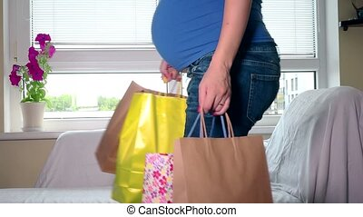 Smiling pregnant woman sit on sofa with shopping bags and stroke her big tummy