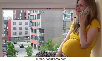 smiling pregnant woman talking on her smartphone sitting on window sill