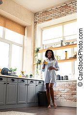 Smiling pregnant woman touching her belly in the kitchen.