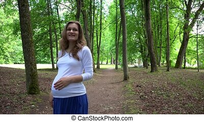 smiling pregnant woman walks alone in park and strokes her...