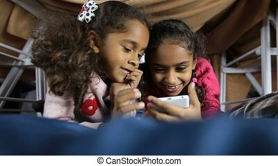 Smiling preschool girls browsing web on smartphone