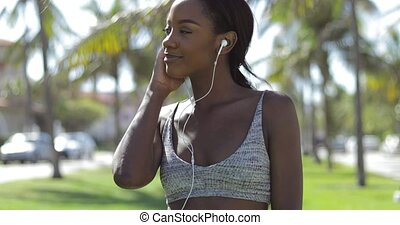 Smiling pretty black woman listening to music