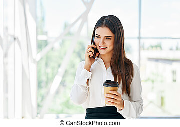 Smiling pretty businesswoman talking on phone holding cup of coffee in open space modern office
