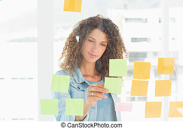 Smiling pretty designer looking at sticky notes on window in...