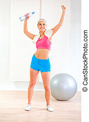 Smiling pretty fitness girl with towel and bottle of water rejoicing success