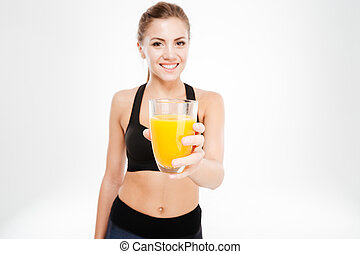 Smiling pretty fitness woman showing orange juice glass ...