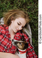 Smiling pretty girl lies on the grass with foxterrier.