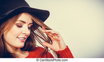 Smiling pretty girl with brown hair and black hat.