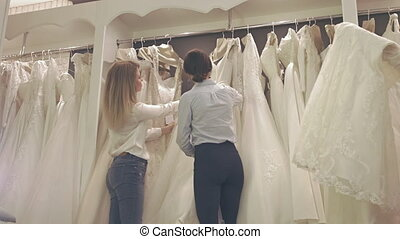 Smiling Pretty Group of Brides Chooses White Dress at Shop...