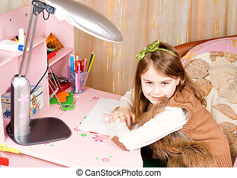 Smiling pretty little girl at her desk