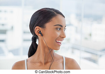 Smiling pretty model in sportswear listening to music