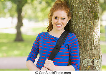 Smiling pretty redhead leaning against a tree