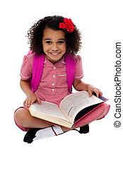 Smiling pretty school girl reading a book