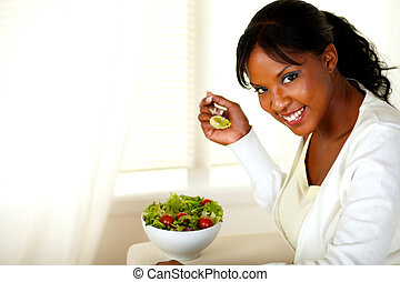Smiling pretty woman eating green salad