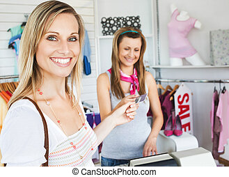 Smiling pretty woman giving her card to the saleswoman in a...