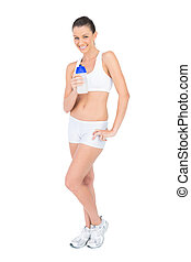 Smiling pretty woman in sportswear holding flask