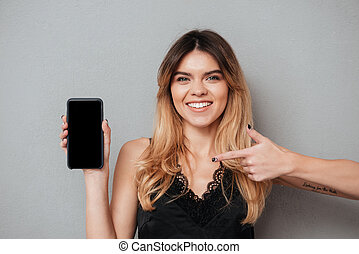 Smiling pretty woman pointing finger at blank screen mobile phone