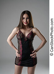 Smiling pretty woman posing in erotic negligee