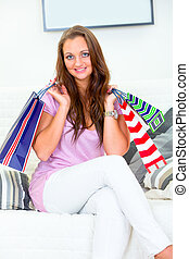Smiling pretty woman sitting on sofa at home and holding shopping bags in hands