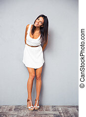Smiling pretty woman standing in trendy white dress