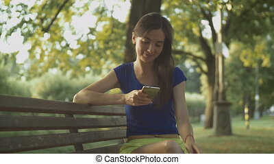 Smiling pretty woman texting on cellphone in park