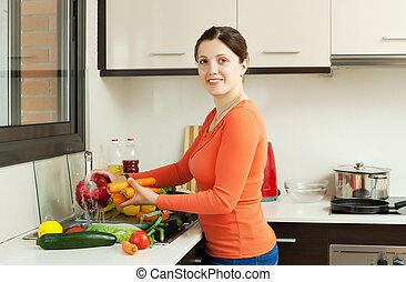 Smiling pretty woman washing fresh vegetables - Smiling...