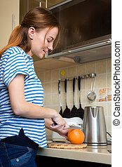 Smiling pretty young pregnant woman cutting orange