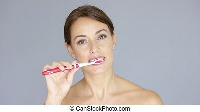 Smiling pretty young woman brushing her teeth with a plastic...