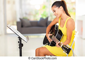 smiling pretty young woman playing guitar at home