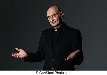 Smiling priest standing and inviting you over black...
