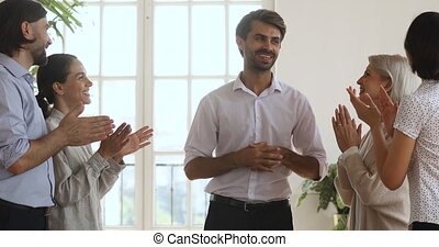 Excited by good project results younger and older colleagues applauding, supporting happy male boss team leader. Smiling proud glad employees praising encouraging shy pleasant supervisor in office.