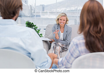 Smiling psychologist talking to a couple during therapy...