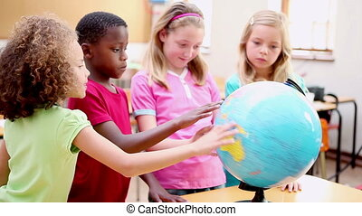 Smiling pupils looking at a globe