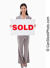 Smiling real estate agent with sold sign