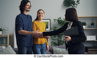Smiling realtor giving key to new owners and shaking hands,...