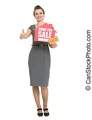 Smiling realtor showing thumbs up and home for sale sold sign