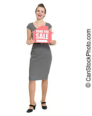 Smiling realtor with home for sale sign isolated