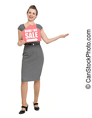 Smiling realtor with home for sale sign showing copy space. HQ photo. Not oversharpened. Not oversaturated