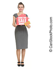 Smiling realtor with home for sale sold sign isolated