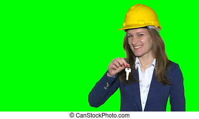 Smiling realtor woman with helmet giving key to customer man hand