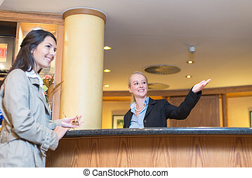 Smiling receptionist helping a hotel guest