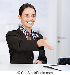 Smiling Receptionist Offering Handshake At Counter -...