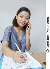 Smiling receptionist talking on phone
