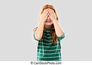 smiling red haired girl with eyes closed by hands