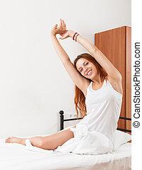Smiling red-haired sensual girl in shirt awaking on white...