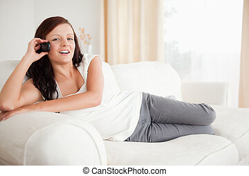 Smiling red-haired woman on the phone relaxing on a sofa