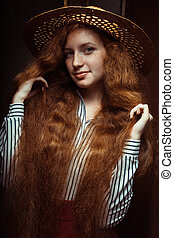 Smiling redhead model with long curly hair in straw hat posing near the old door
