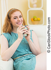 Smiling redhead sitting on the couch and holding mug