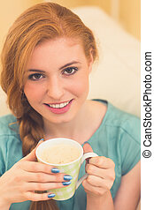 Smiling redhead sitting on the couch having coffee looking at camera at home in the living room