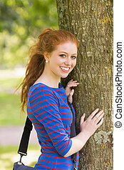 Smiling redhead student leaning on